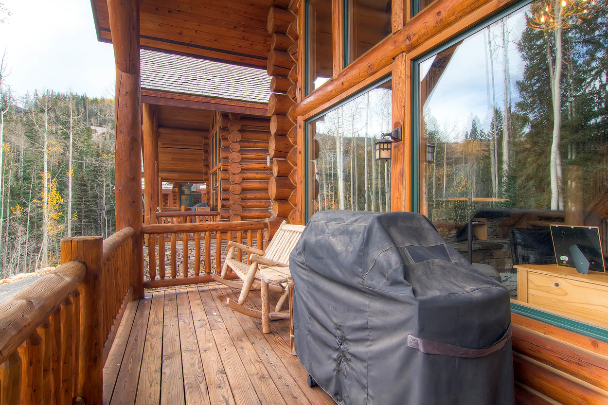 The deck is located off of the living room, with a gas grill and pine wood seating.