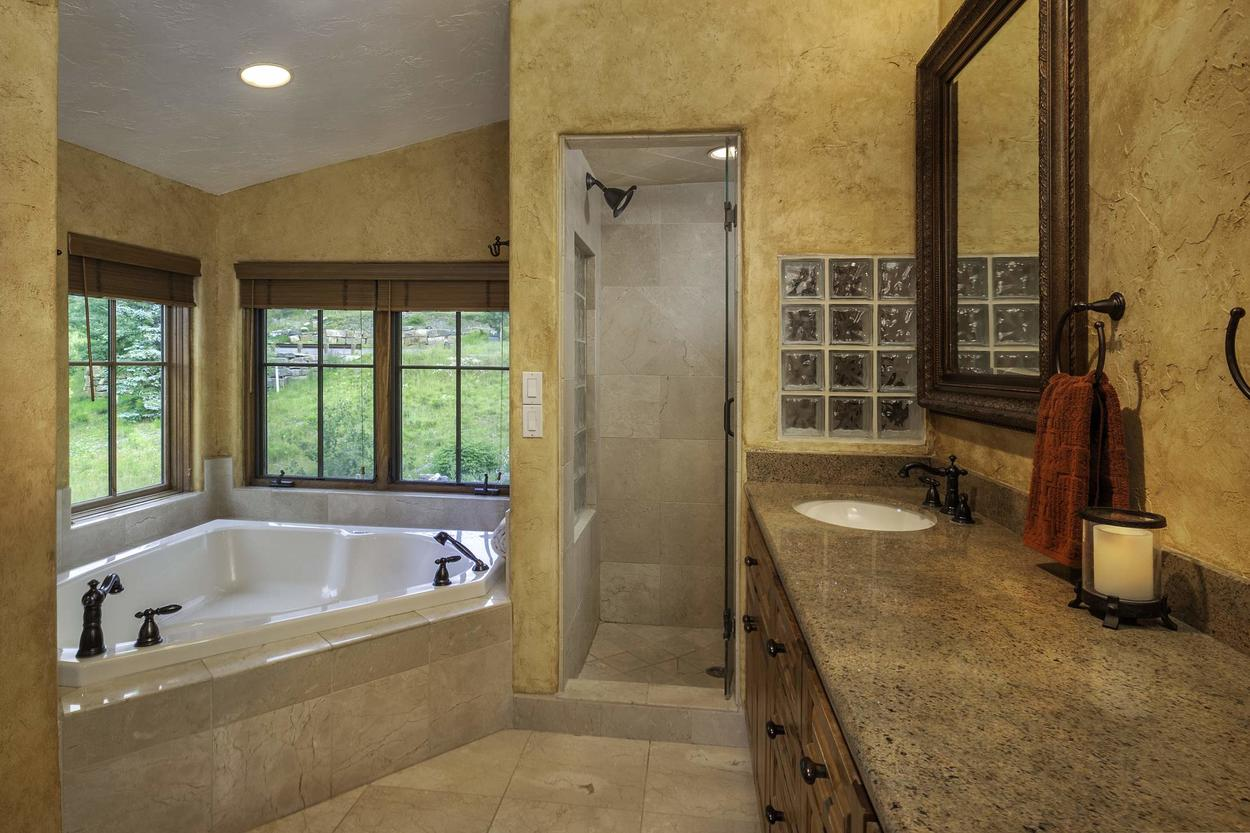 The en-suite master bathroom features a large jetted tub and a separate walk in shower as well as a double sink vanity.