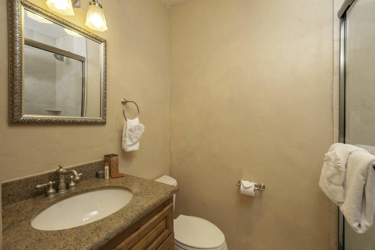 Guest Bathroom #3 on the 3rd floor features a single sink vanity, large mirror and a shower/tub combo.