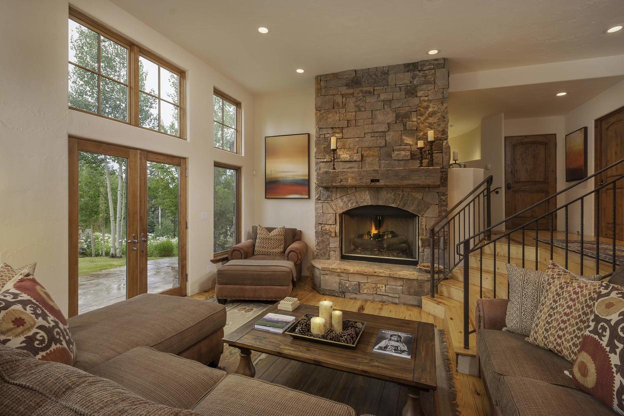 The sunken living room offers plenty of comfortable seating around the fireplace - it's the perfect place to warm up!
