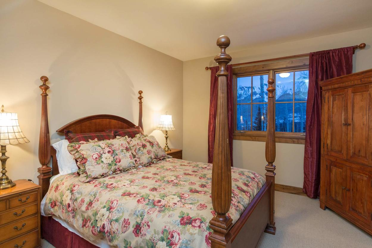The lower level Guest Bedroom 2 features a queen bed and en suite bathroom.
