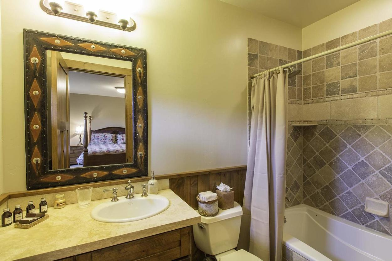The en suite for guest bedroom 2 features a shower tub combo and single sink vanity.