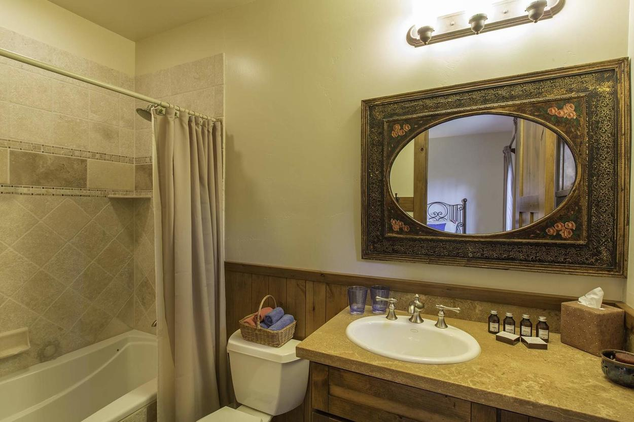 The en suite for the twin bedroom has a single sink vanity and a shower/tub combo.