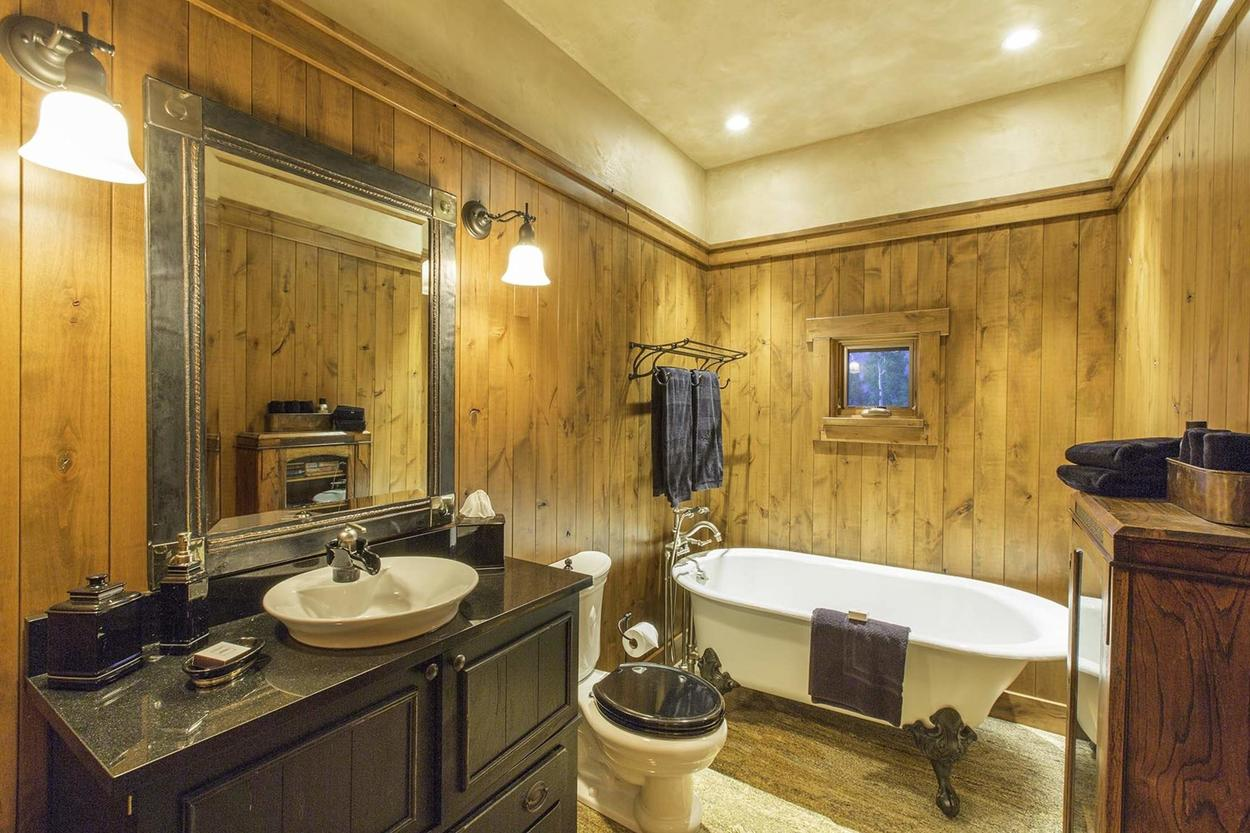 The bathroom off the office features a single sink vanity and a bear claw tub.