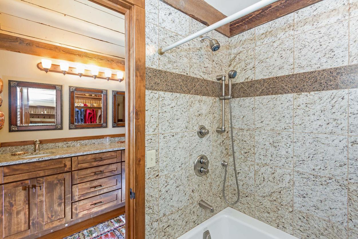 The en suite bathroom features a shower/tub combo and a single sink vanity.