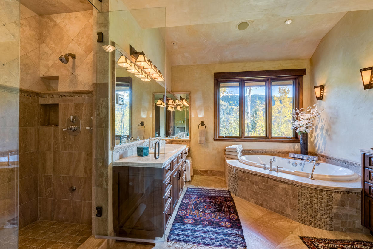 Back inside, the master en suite has a walk-in shower, two vanities, and a jetted tub that maintains that gorgeous view.