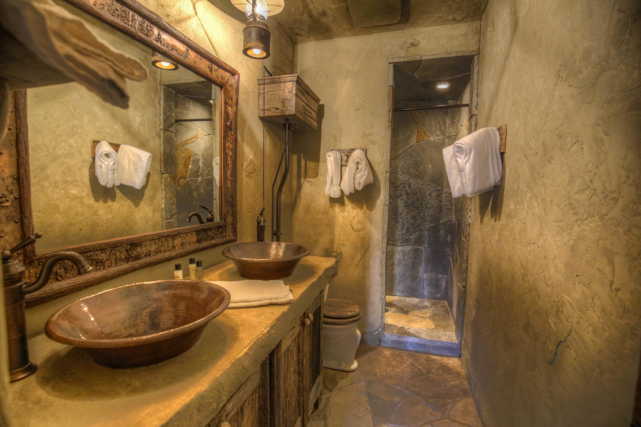 Basin sinks and stone walls create a rustic feel in this bathroom.