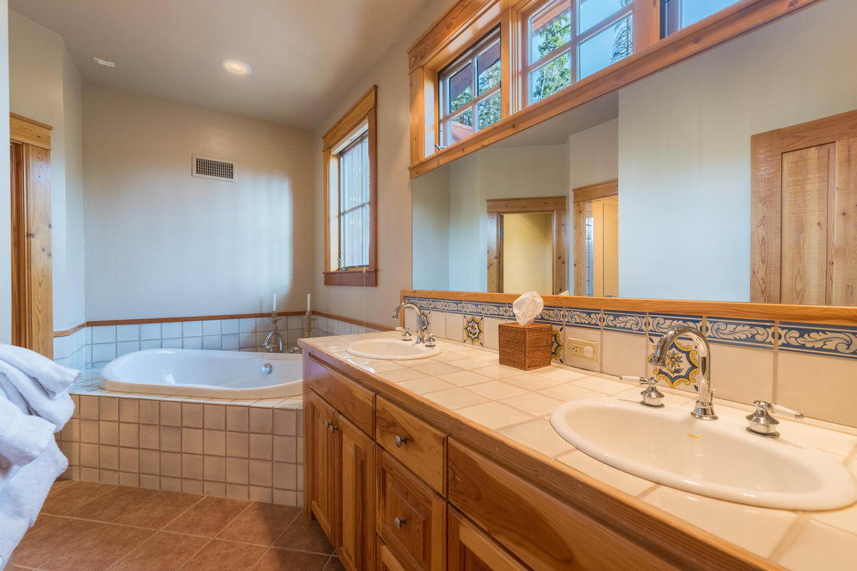 The ensuite for Guest Bedroom 2 has a soaking tub, shower and dual sinks.