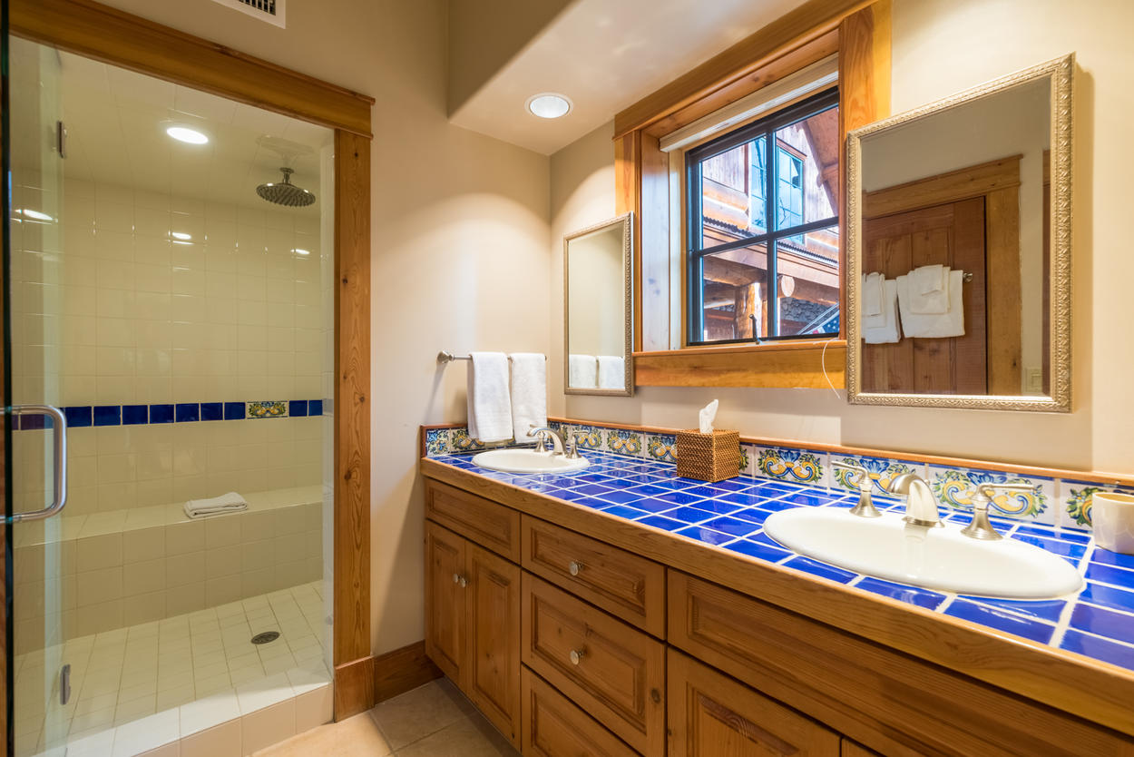 The ensuite bathroom for guest bedroom 5 features dual sinks and a shower.