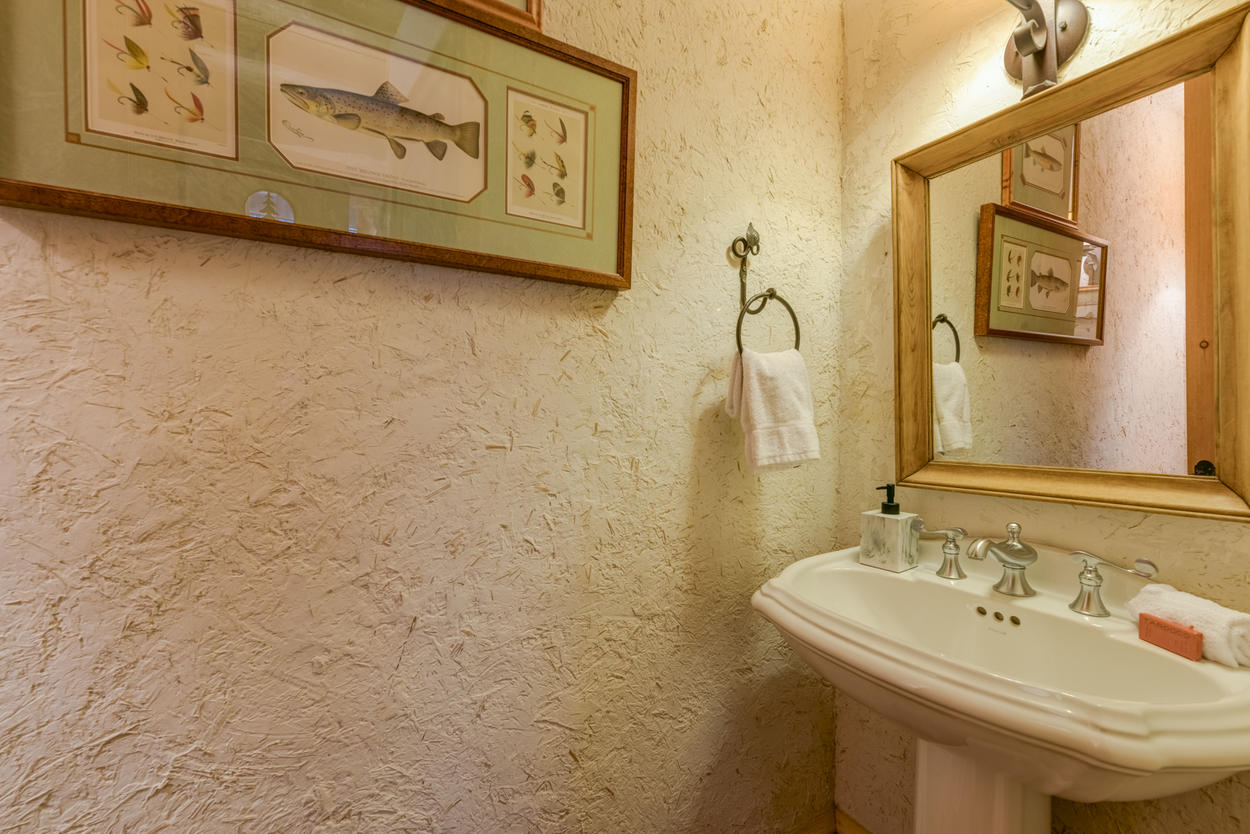 The powder room is located on the main level of the home, adjacent to the laundry room.