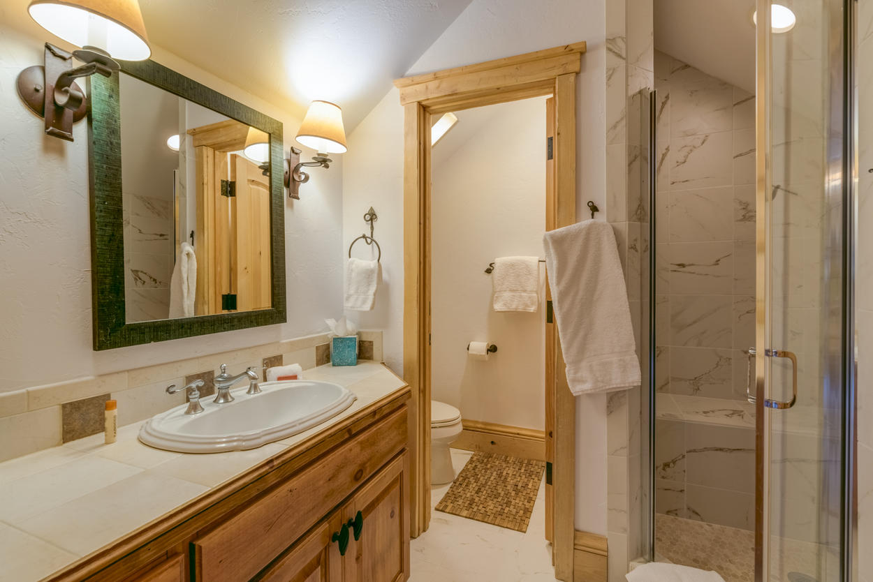 The ensuite for the bunk room features a walk-in shower and a single sink.