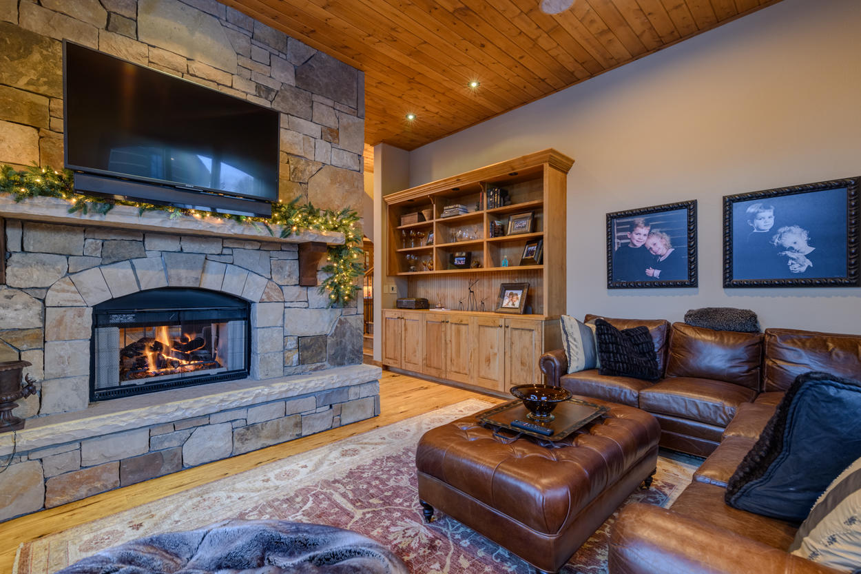 On the other side of the fireplace is the welcoming Media Room, with a leather sectional and flat screen tv