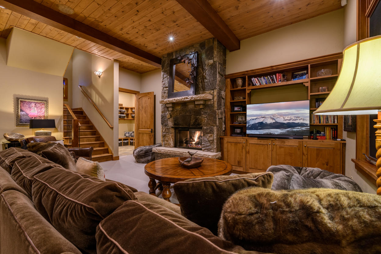 Downstairs, the den is a comforting space with plenty of plush seating to offer