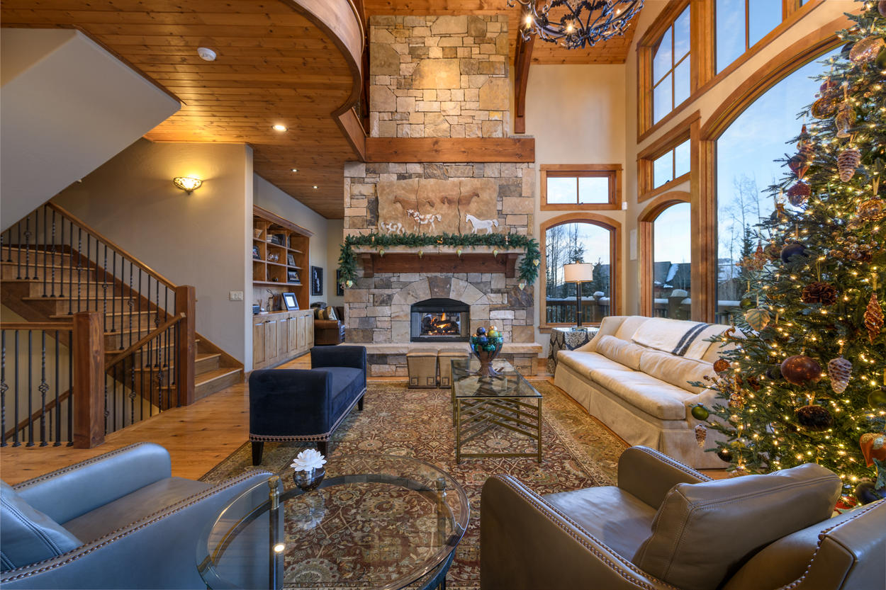 The living room has enormous windows and rustic stonework surrounding a gas fireplace