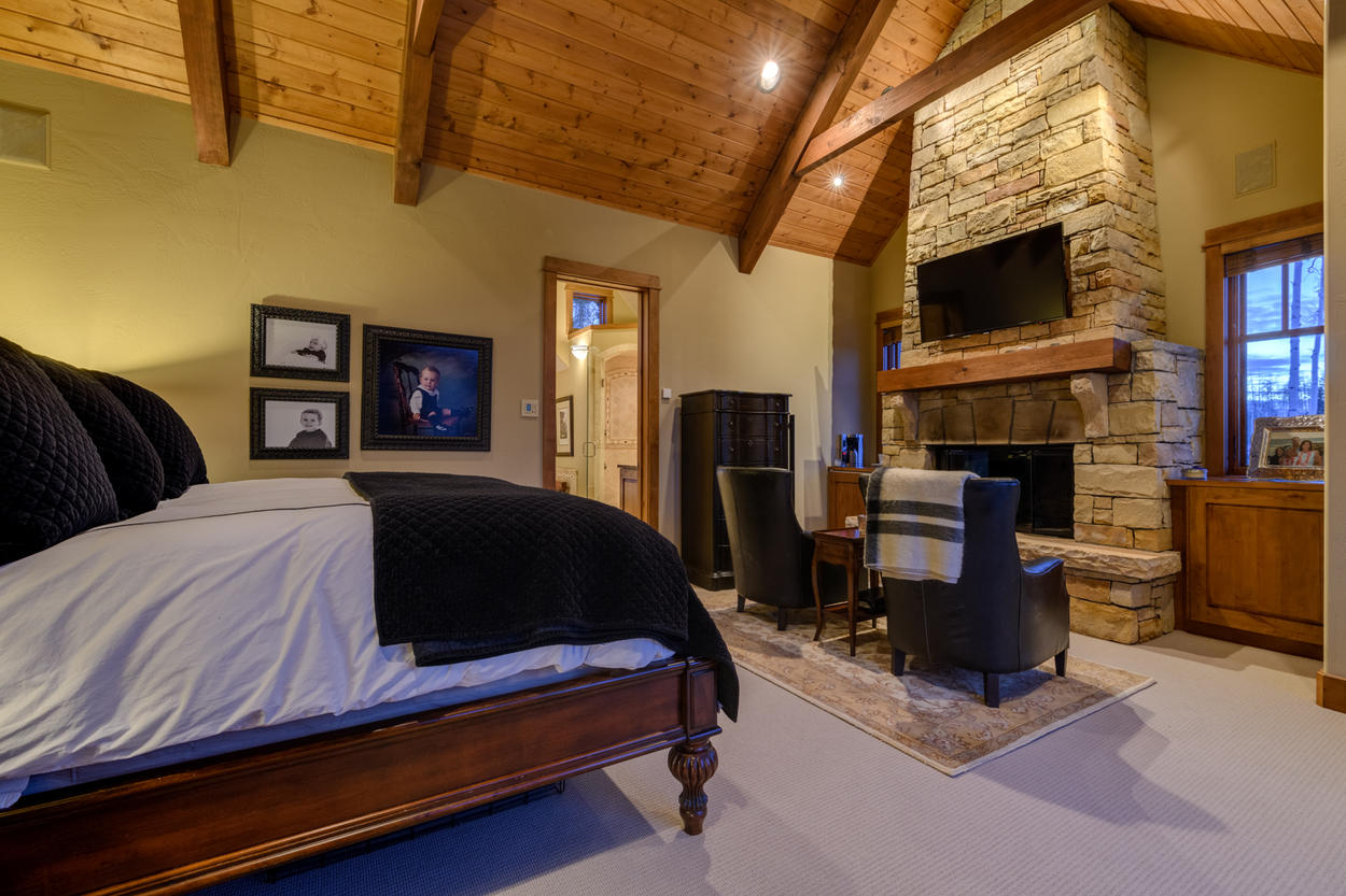On the upper level of the home, the Master features vaulted ceilings that meet at the pinnacle of a stone fireplace