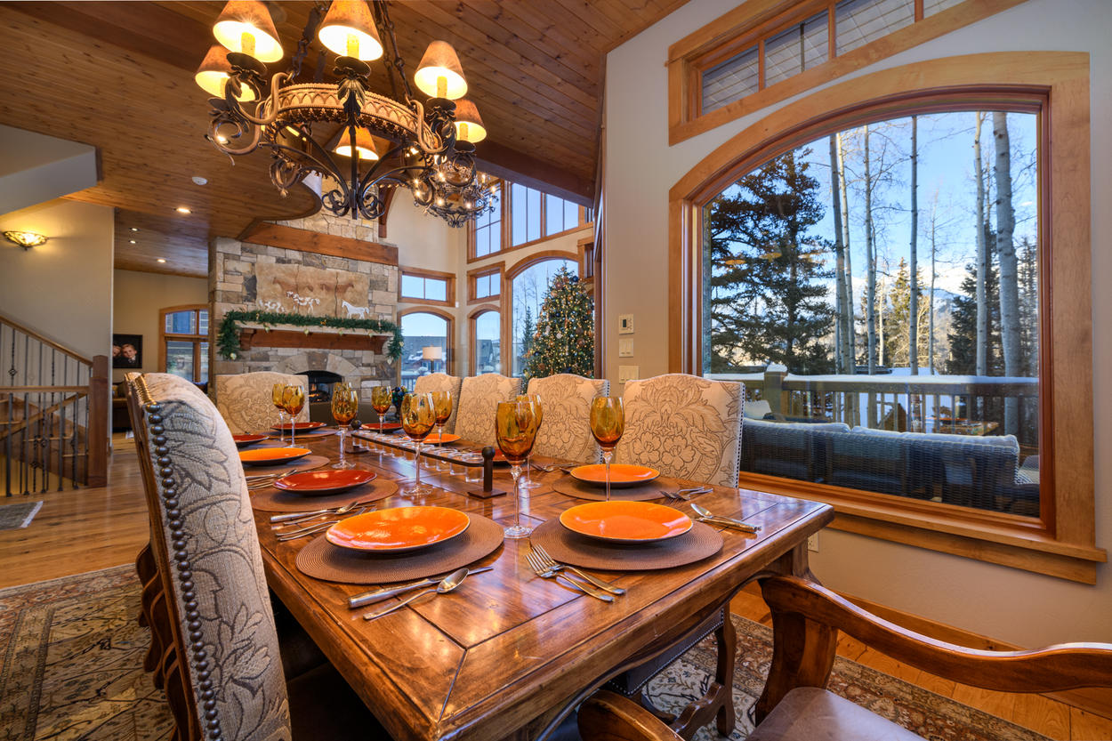 Just off the kitchen, an elegant dining space looks out at the peaks beyond and seats an additional 10 guests