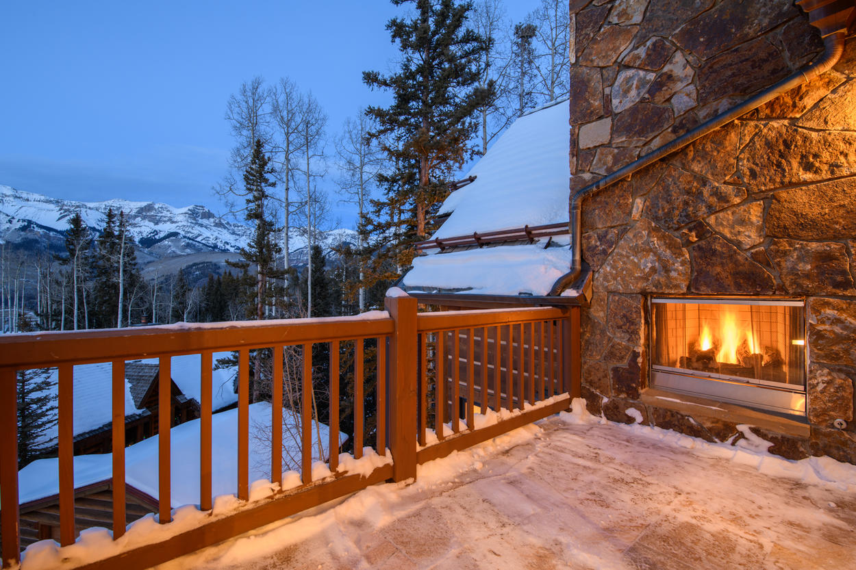 An outdoor fireplace provides warm ambiance to autumn evenings spent on the private balconies of this home
