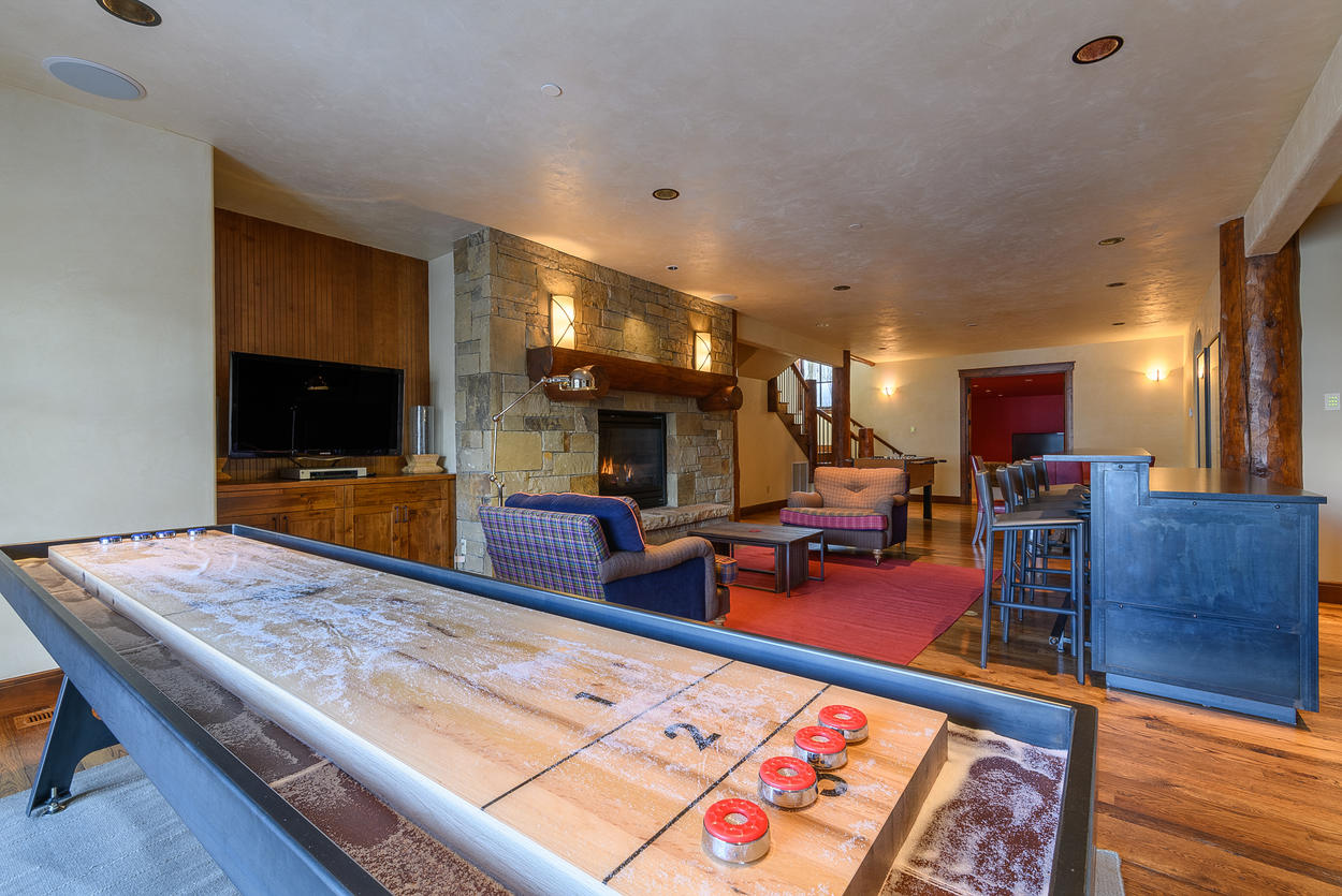 On the lower level, the game room features a foosball table, shuffle board, TV and gas fireplace.