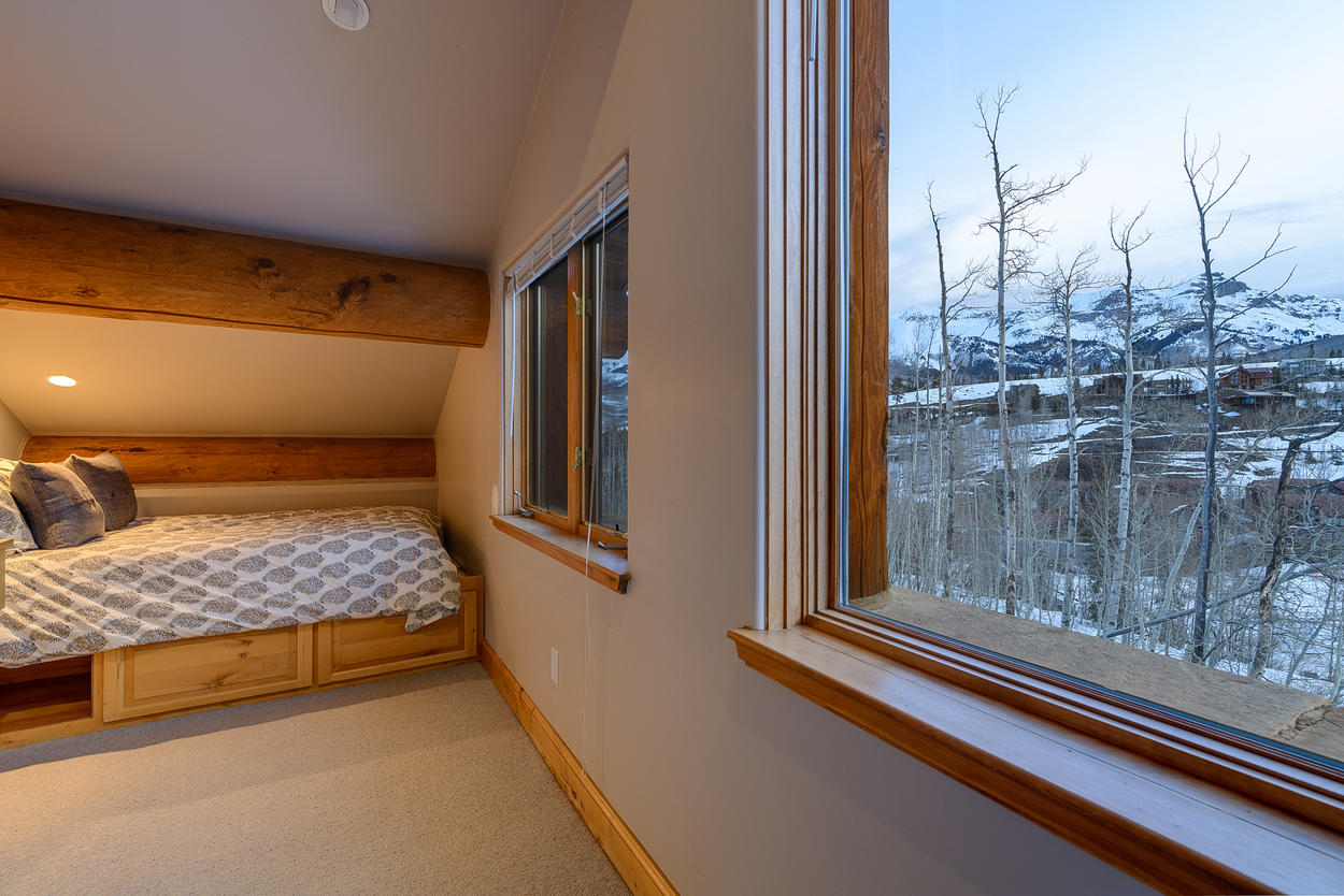 The top level of the guest house has a full-size bed on a cozy pitched ceiling.