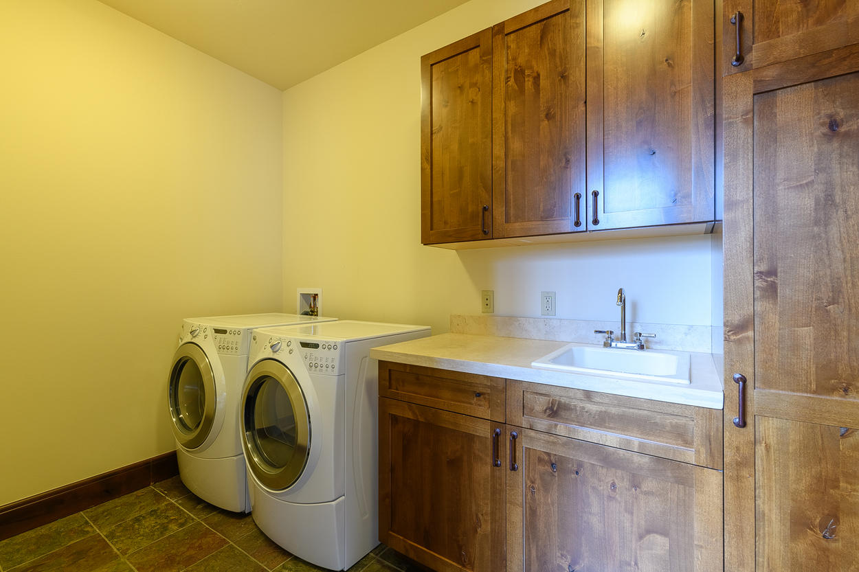 The lower level laundry room features a washer, dryer, sink, and plenty of storage.