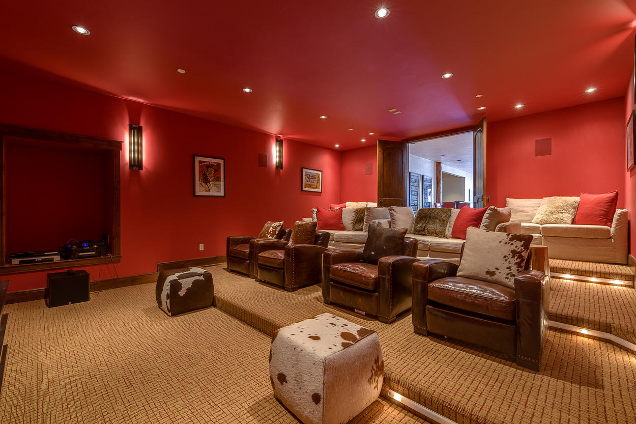 The home theater is also located on the lower level, and has a large TV with a combination of sofas and overstuffed leather chairs.