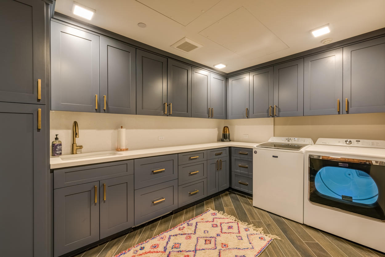 The laundry room has a washer, dry, sink, and plenty of storage.