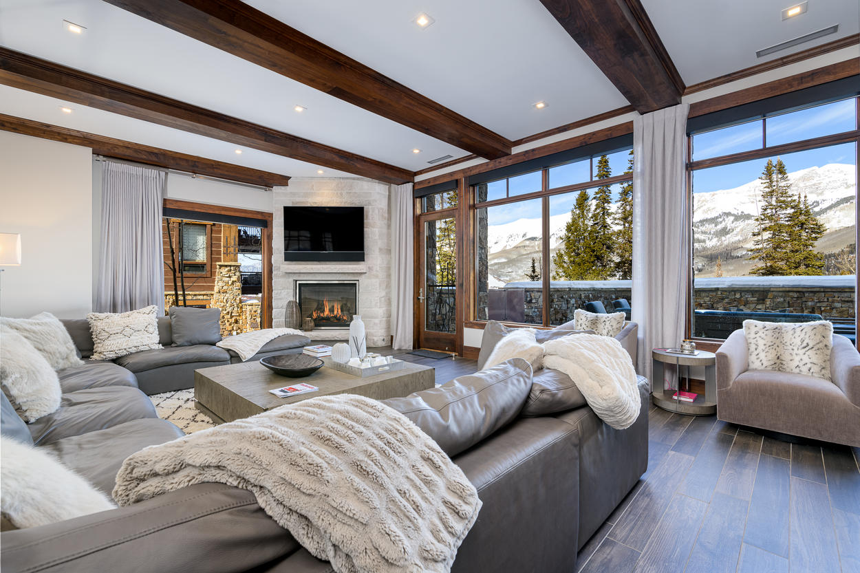 Exposed wood beams along the ceiling frame the elegant living space