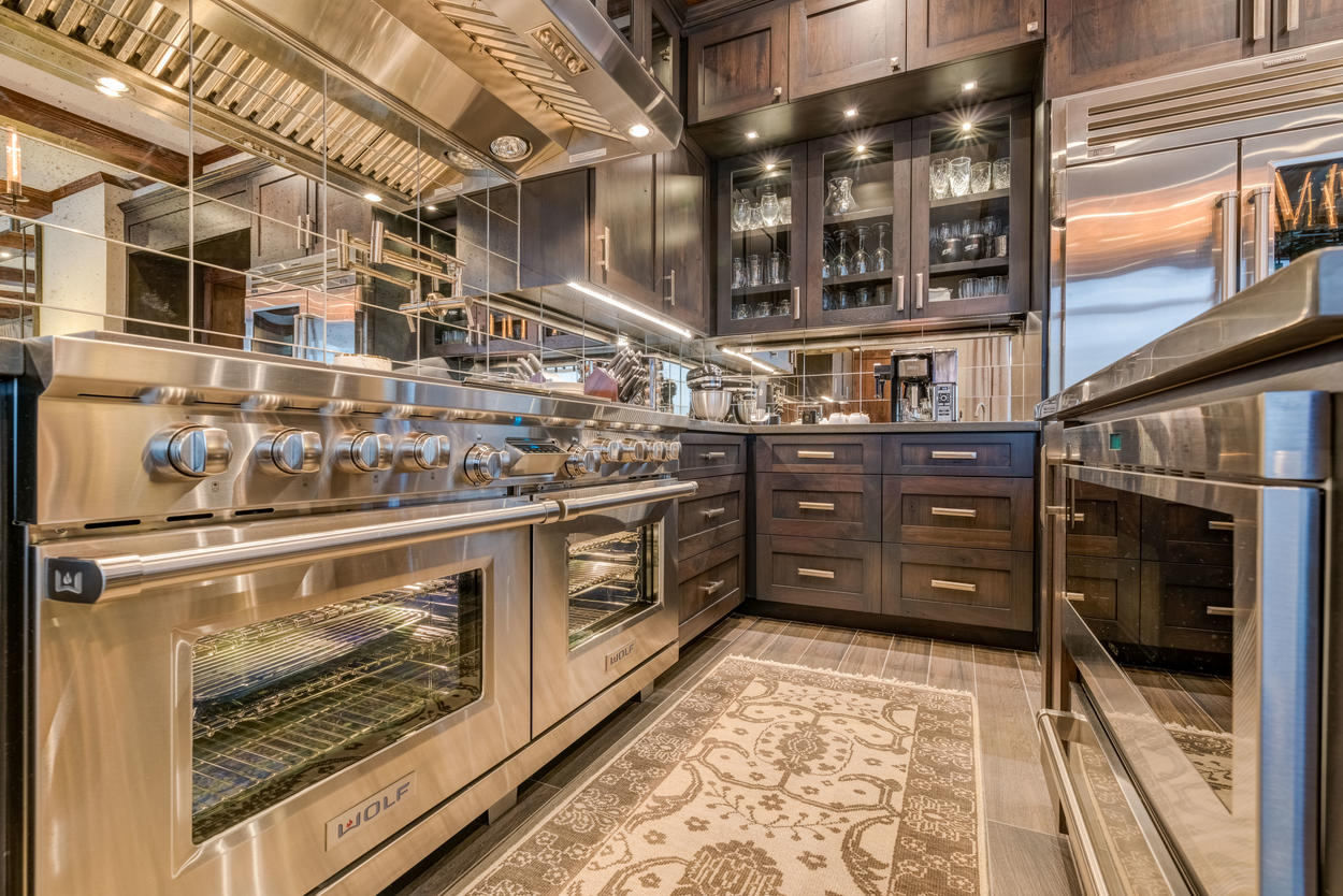 The kitchen includes a double oven and an 8-burner gas range.
