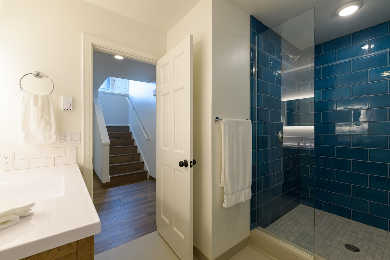 There's a shared full bathroom on the first floor that features a frameless walk-in shower and large sink.