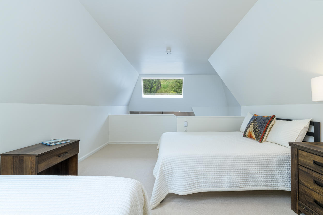 The loft bedroom is light and airy, simple and cozy.