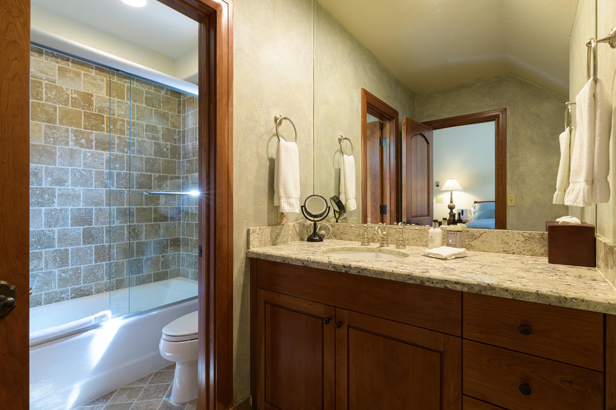 The 4th floor guest bedroom has an attached ensuite with a single sink and separate are with a shower/tub combination.