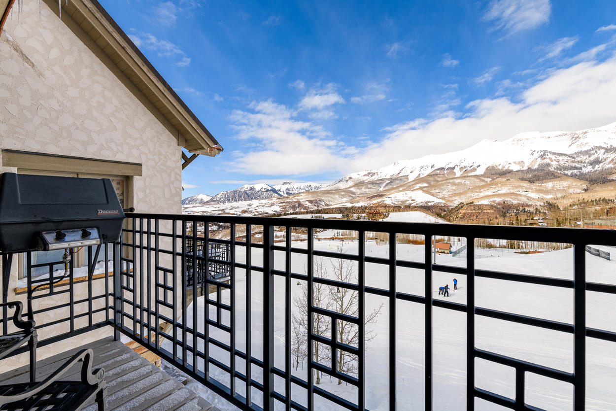 The upper deck features a gas grill and outdoor seating amid Telluride's stunning scenery.