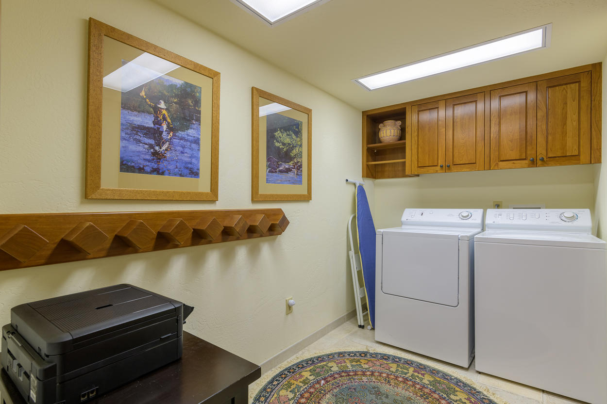 The laundry room has a washer, dryer, and storage.