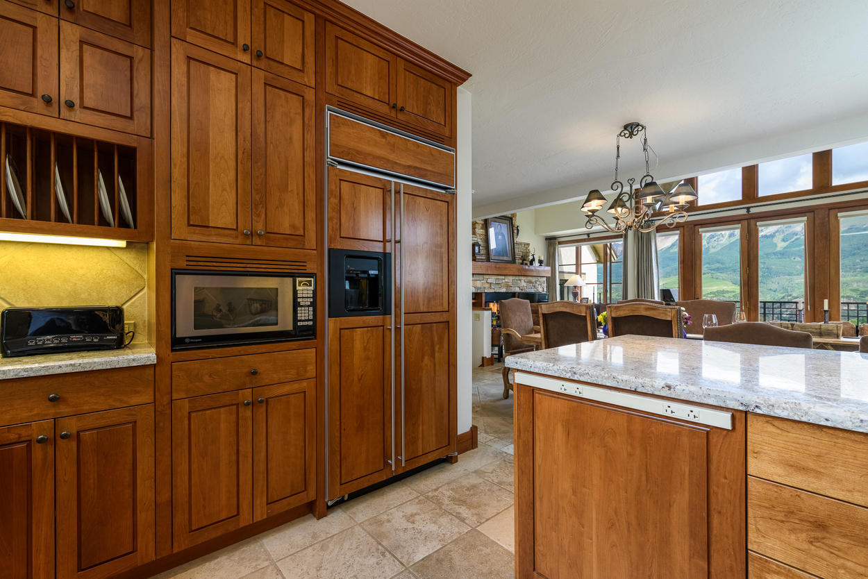 The kitchen features fine wood cabinets and stone countertops.