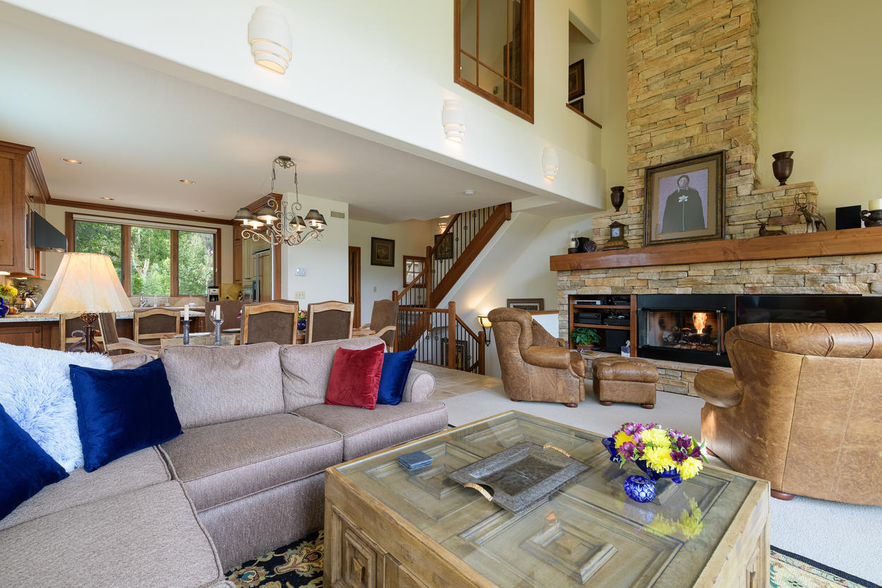 The warm and inviting living room has high ceilings and a large stone fireplace surrounded by plush seating.