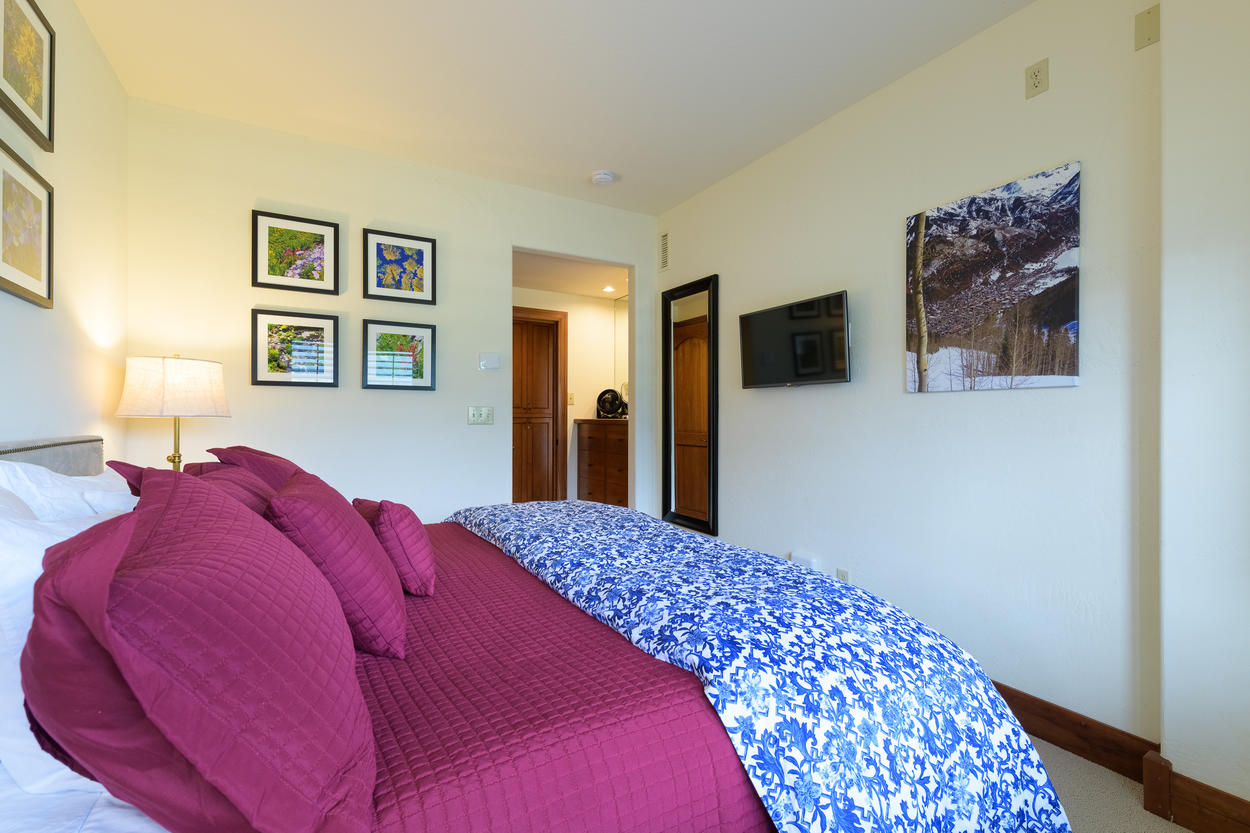 The guest bedroom on the first floor offers fresh decor and a mounted flatscreen TV.