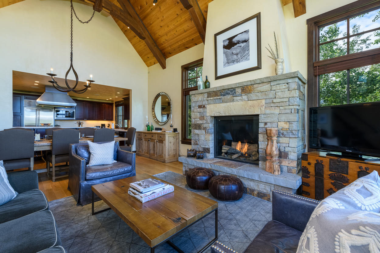 A large stone fireplace in the living room acts as a warm centerpiece.