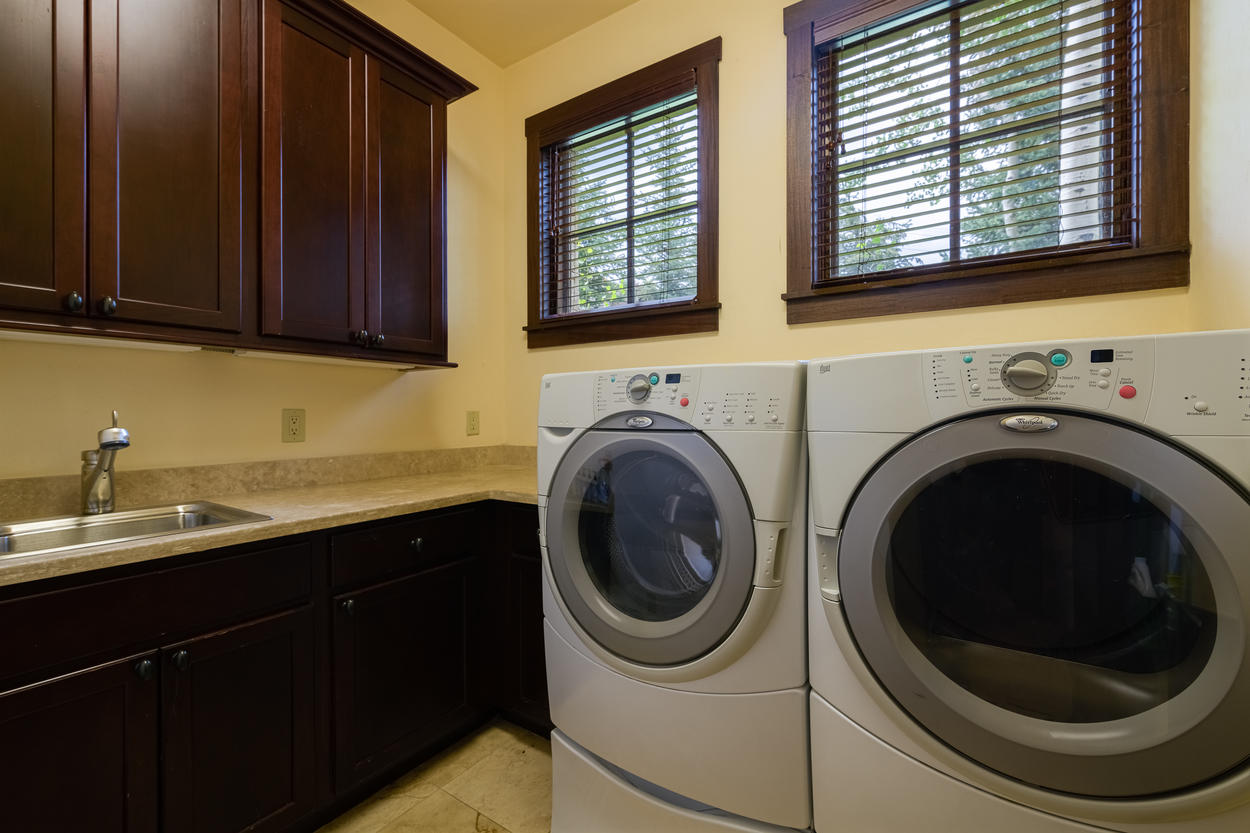 A separate laundry room has a sink and plenty of cabinet storage.