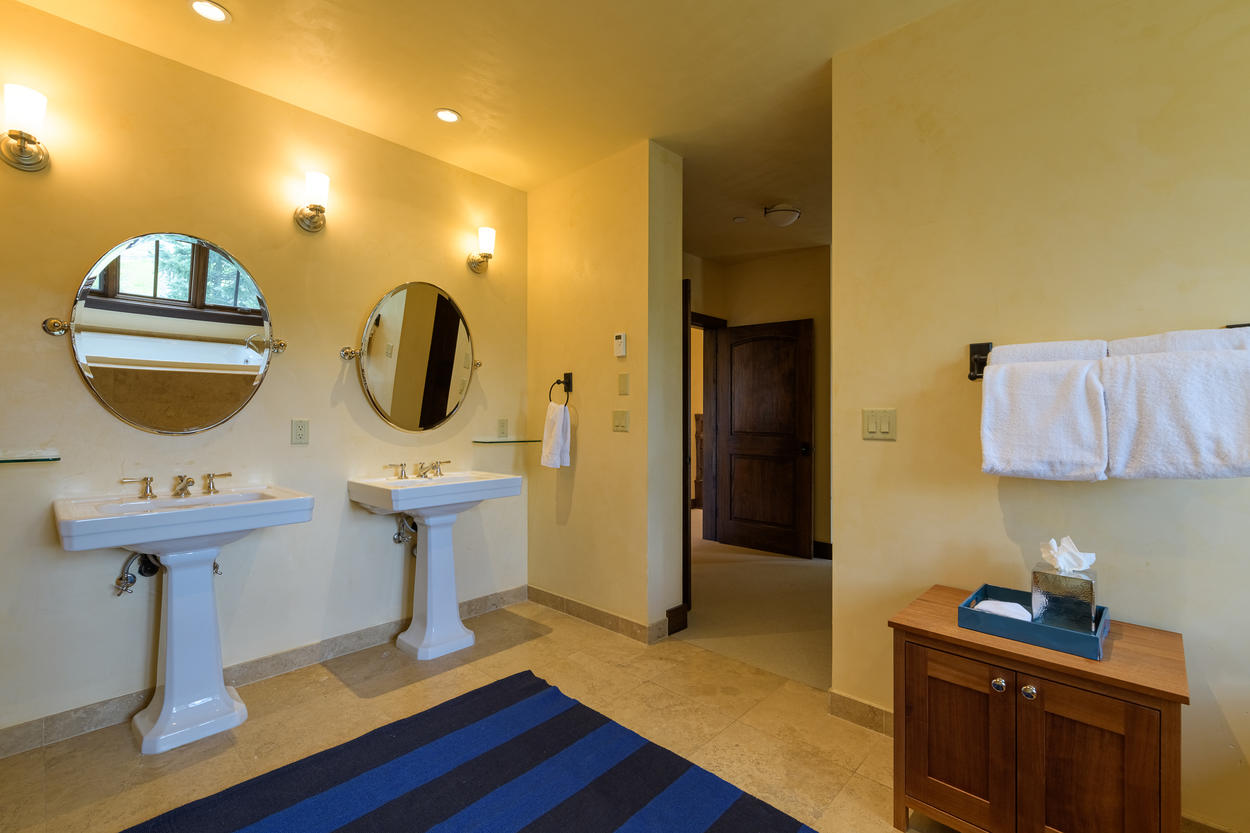 The ensuite bathroom to Guest Bedroom 1 has two pedestal sinks.