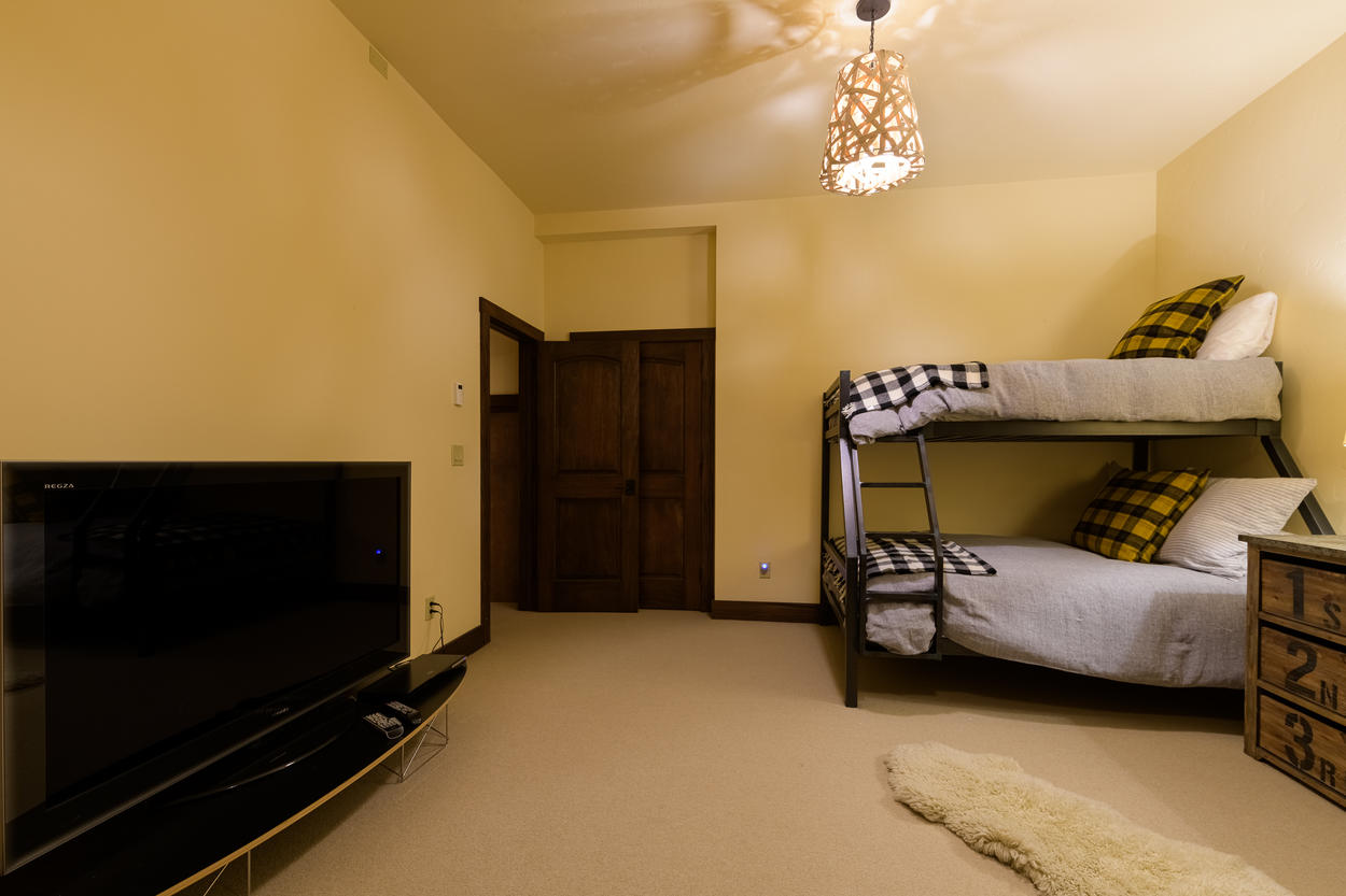 The bunk room is located on the first floor and has its own flatscreen TV.