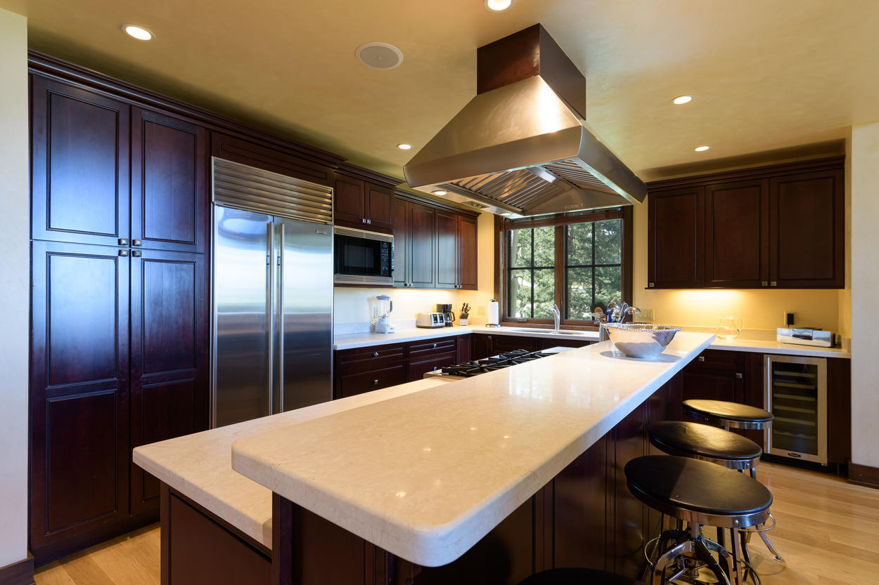 The kitchen features a breakfast bar with additional seating for three guests.