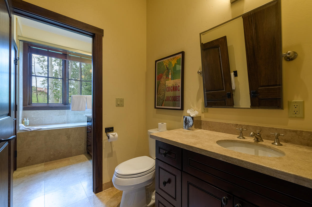 The ensuite of Guest Bedroom 4 has a large vanity, walk-in shower, and tub.