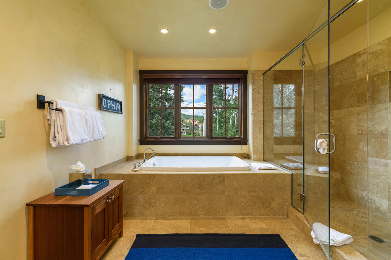 The large soaking tub is set beneath a window that looks out between the aspens.