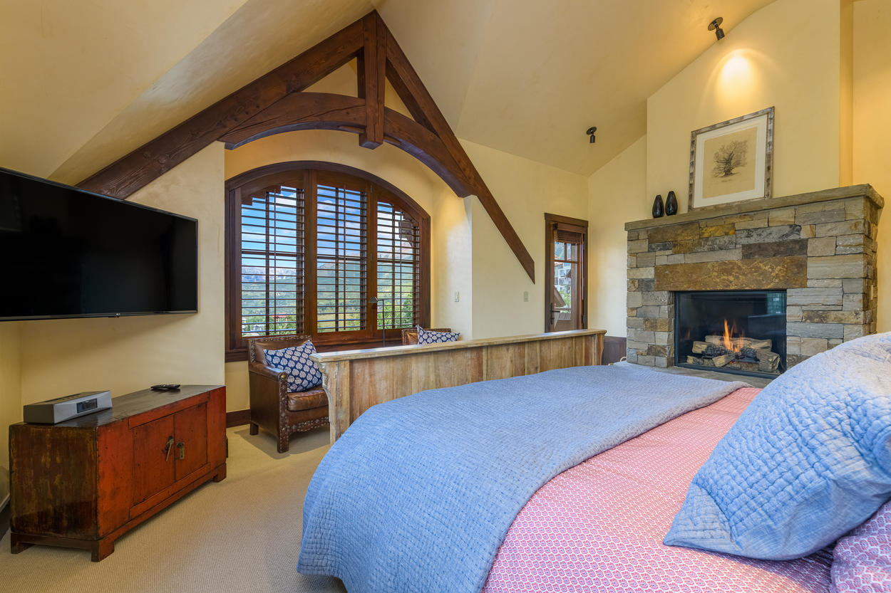 There's a large mounted flatscreen TV in the corner of the Master Bedroom with private balcony access in the other corner.