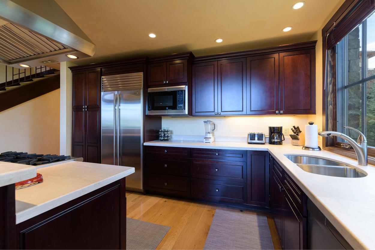 Rich wood cabinets line the sleek, modern kitchen.