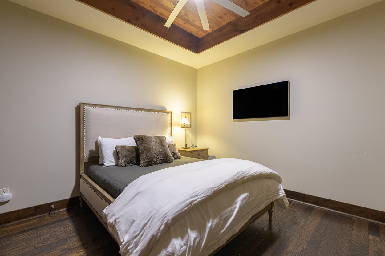 The guest bedroom has high ceilings and a wall-mounted flatscreen TV.