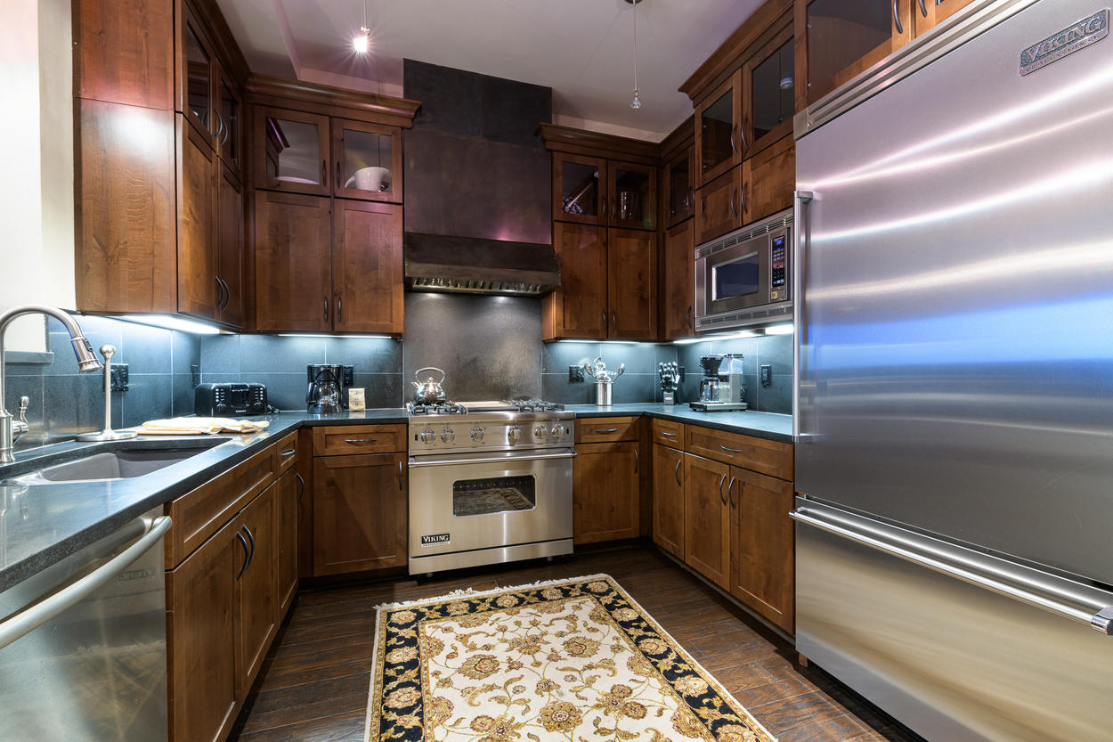 The stainless steel appliances pair well with the rich wood cabinets in the kitchen.