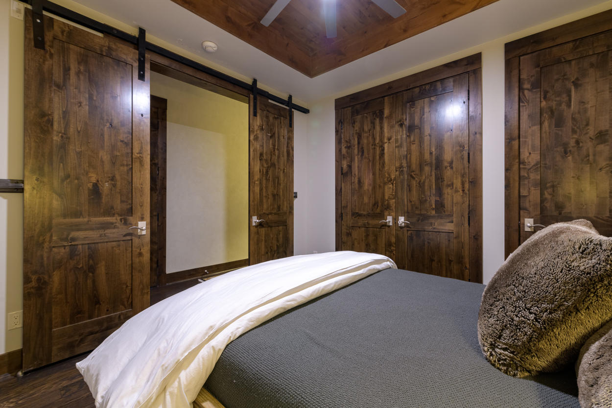 Access the guest bedroom through rich sliding wood barn doors.