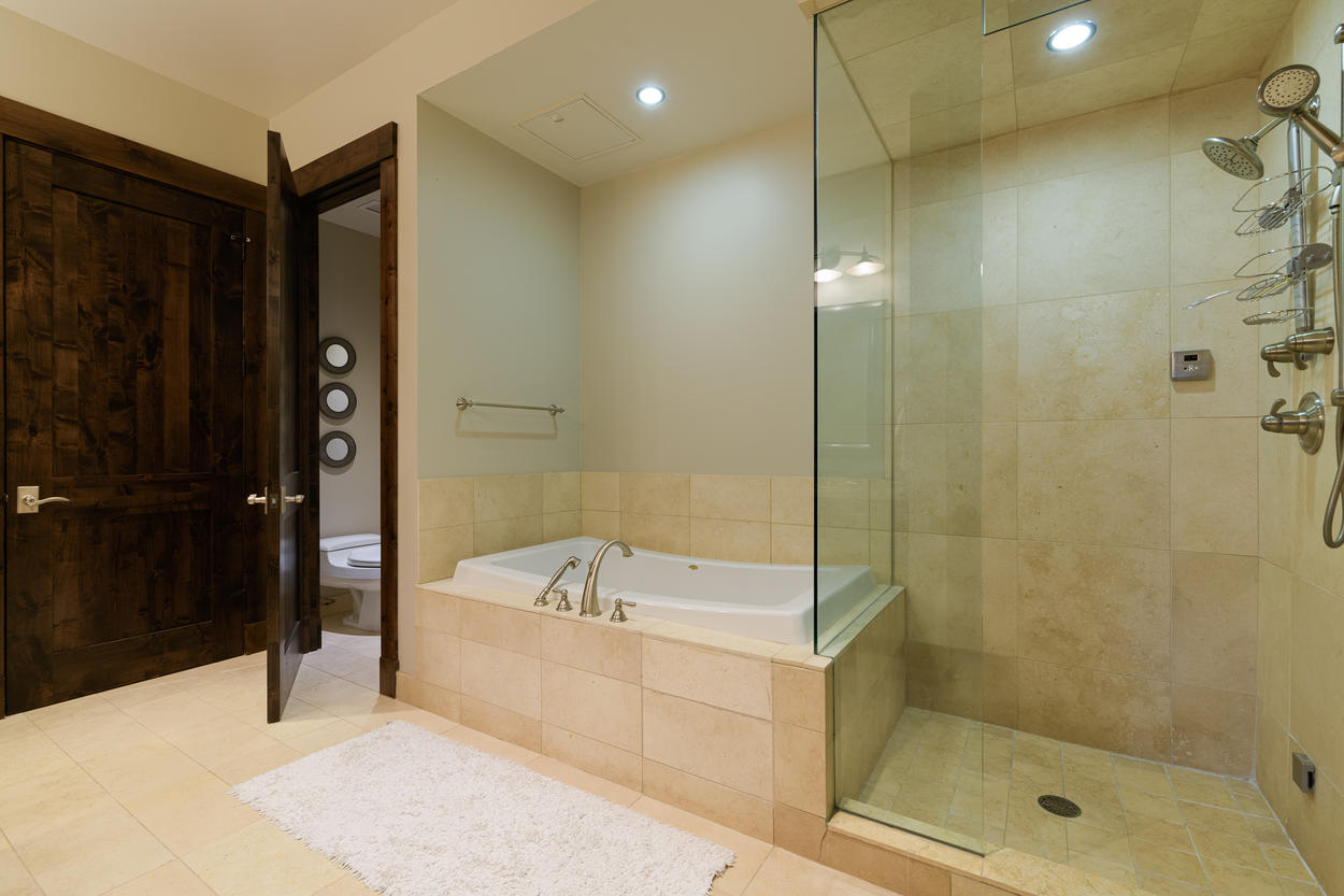 The Master Bath is spacious and modern, with a frameless walk-in glass shower and large tub.