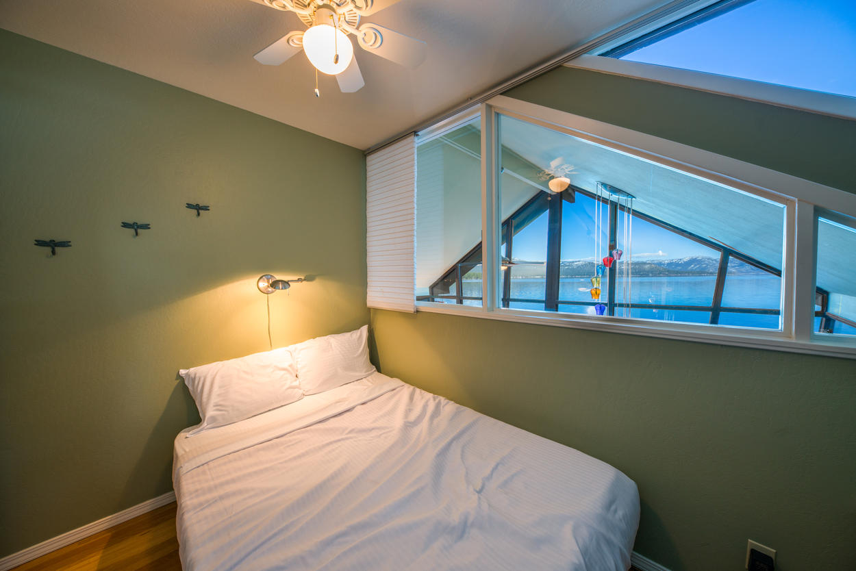 The full guest room on the second floor has views of the lake and looks out upon the main living area.